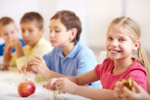 Group-of-kids-having-lunch-girl-smiling-at-camera