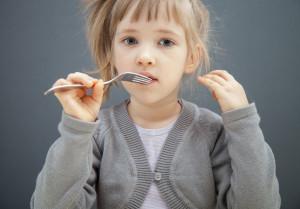 Little girl holding fork